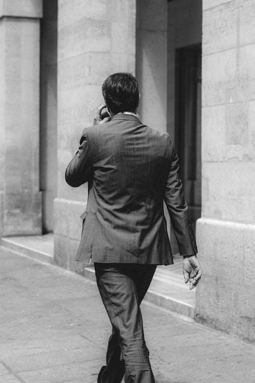 Elegant businessman in suit walking along concrete building