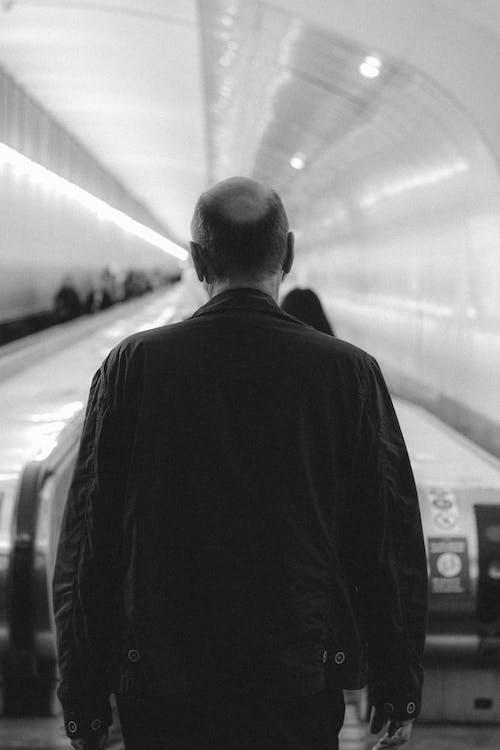 Man walking towards escalator in subway
