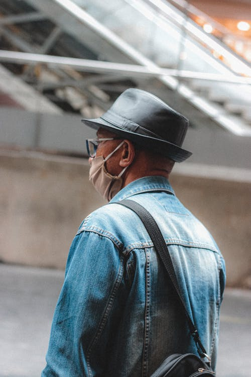 Back view of man in denim jacket and hat with bag wearing protective mask standing near escalator