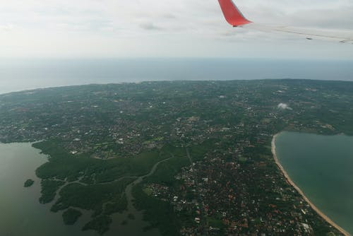 Wing of aircraft flying over coastal city