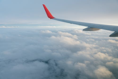 Wing of airplane flying over clouds