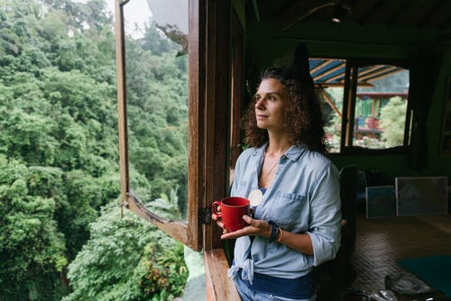 Content woman near window in rural house against rainforest