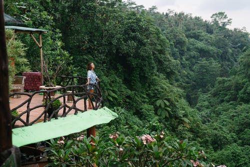 Woman standing on cottage porch against jungle
