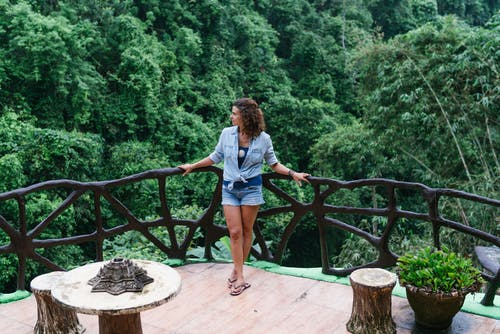 Full body calm female in denim leaning on house balcony railing with arms outstretched and enjoying tropical jungle view in exotic resort