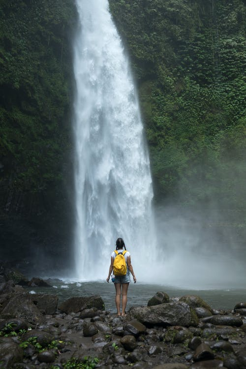 Unrecognizable female traveler admiring majestic waterfall