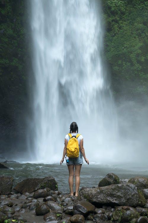 Female backpacker enjoying waterfall streaming from green hills