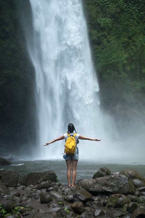 Relaxed woman with outstretched arms admiring waterfall