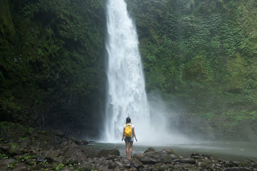 Woman with backpack enjoying scenic waterfall in tropical forest