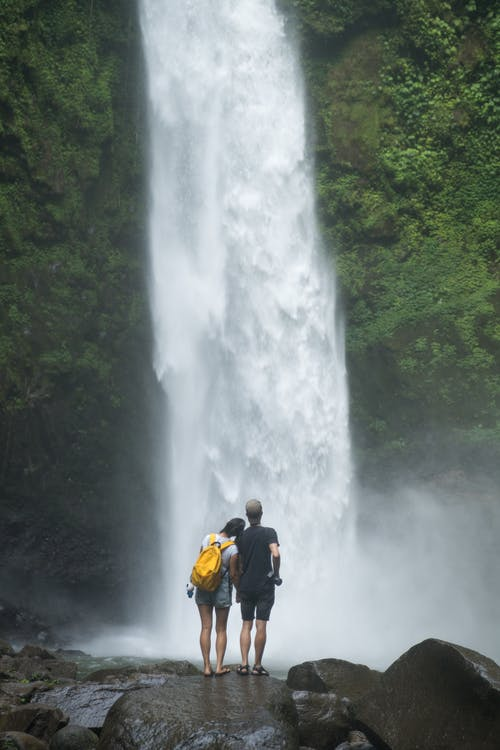 Romantic couple enjoying waterfall in green highlands