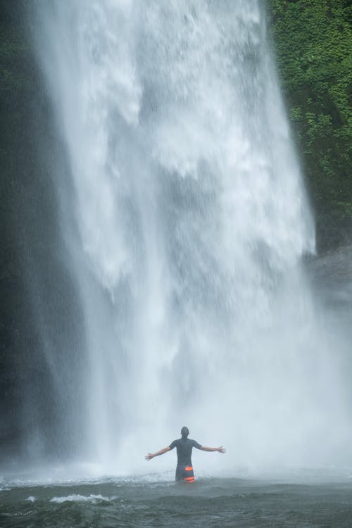 Unrecognizable man with outstretched arms standing in waterfall lake