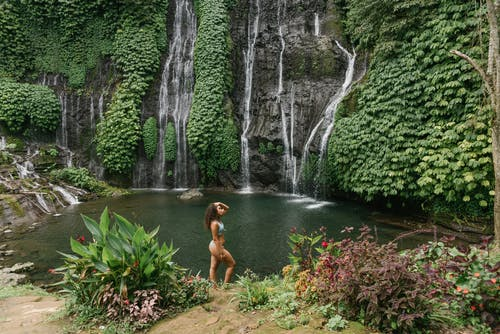 High angle of peaceful young woman in bikini touching hair while standing between tropical plants against waterfall flowing into pond
