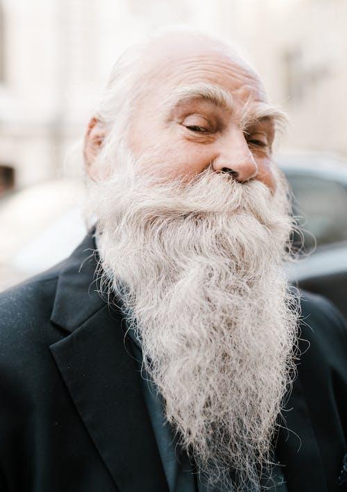 Positive elderly bearded male in elegant blazer