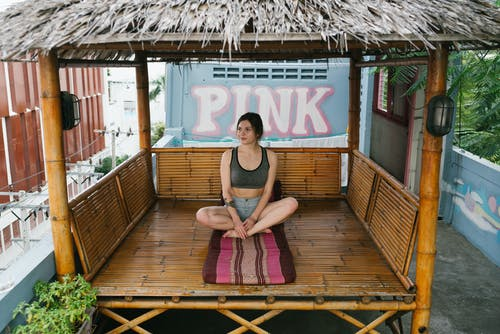 Peaceful young woman sitting in gazebo in Padmasana yoga pose