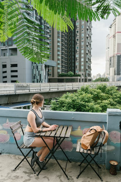Side view of anonymous young woman sitting at wooden table in outdoor cafe near modern buildings and looking away