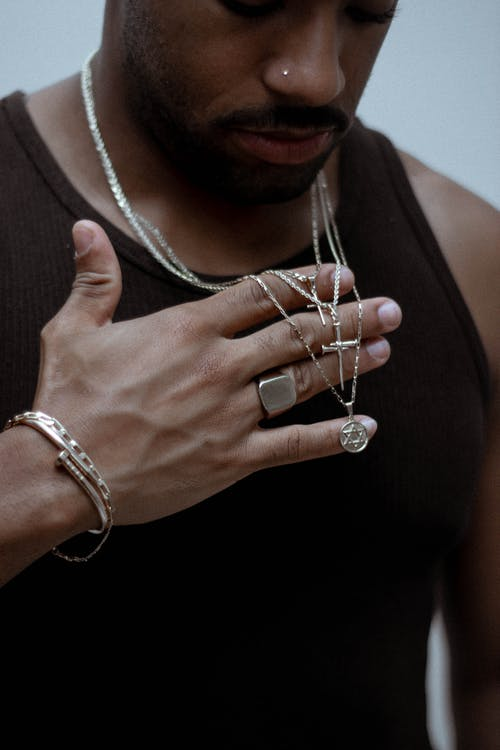 Ethnic man in accessories on neck and hand