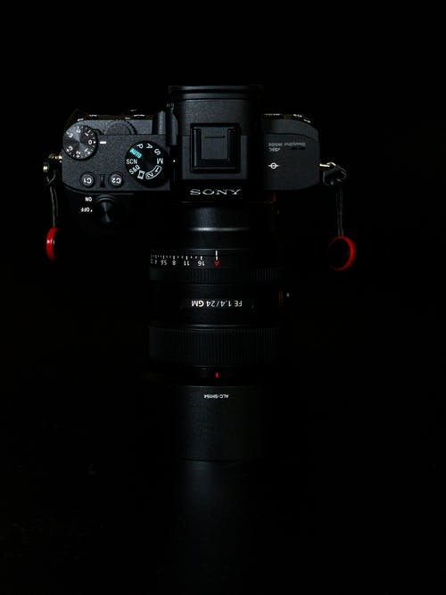 From above of modern digital photo camera with professional zoom lenses against black background