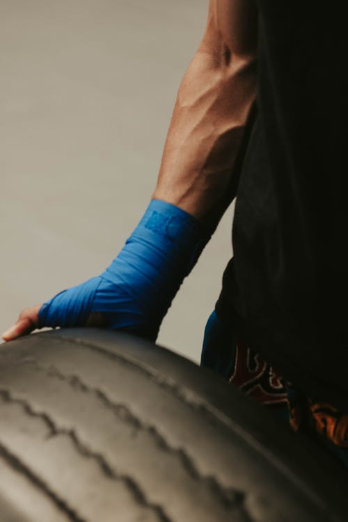 Crop strong male athlete exercising with heavy tire