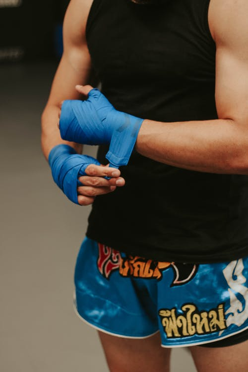 Crop faceless young male fighter in shorts wrapping boxing bandage before training in contemporary gym