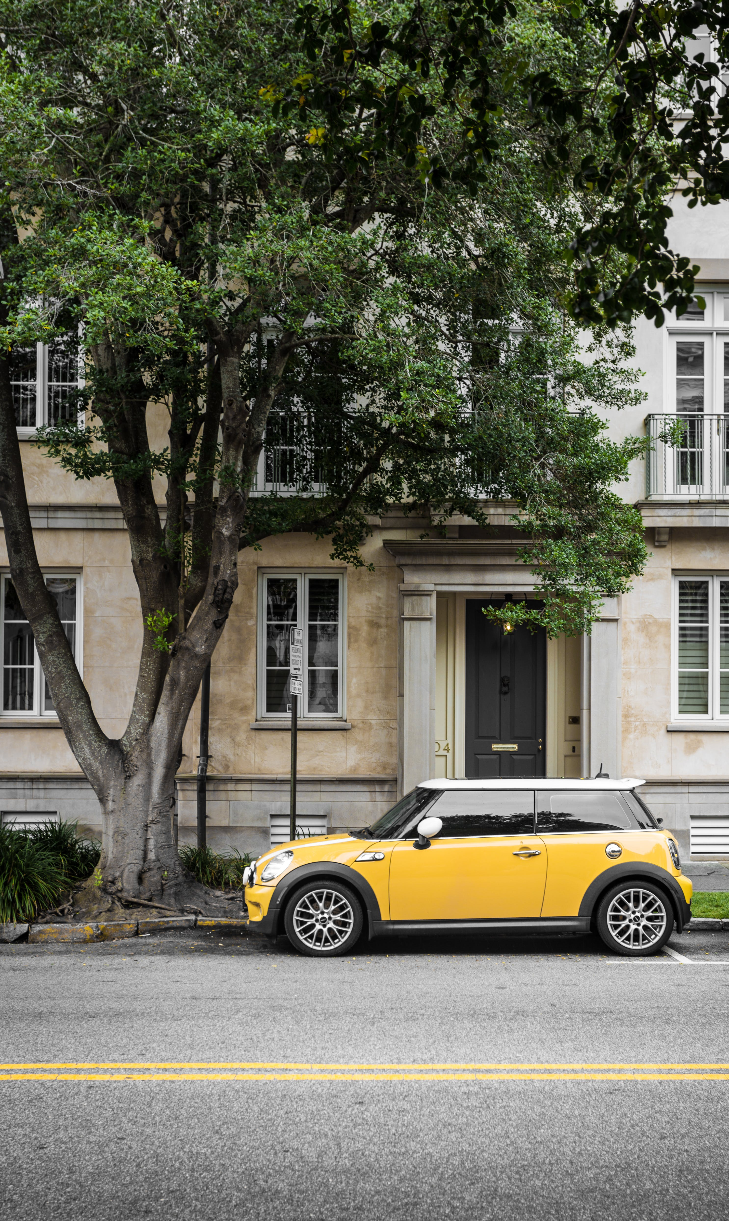 Yellow Mini Cooper Parked Beside White Concrete Building