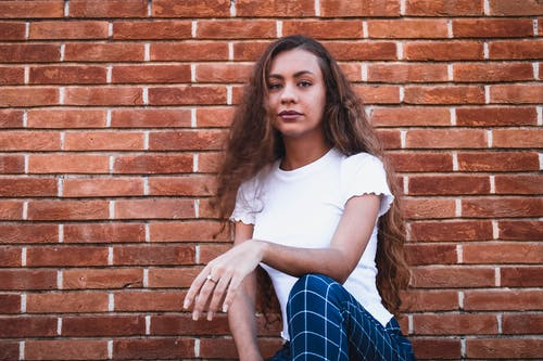 Stylish young lady sitting on haunches near brick building
