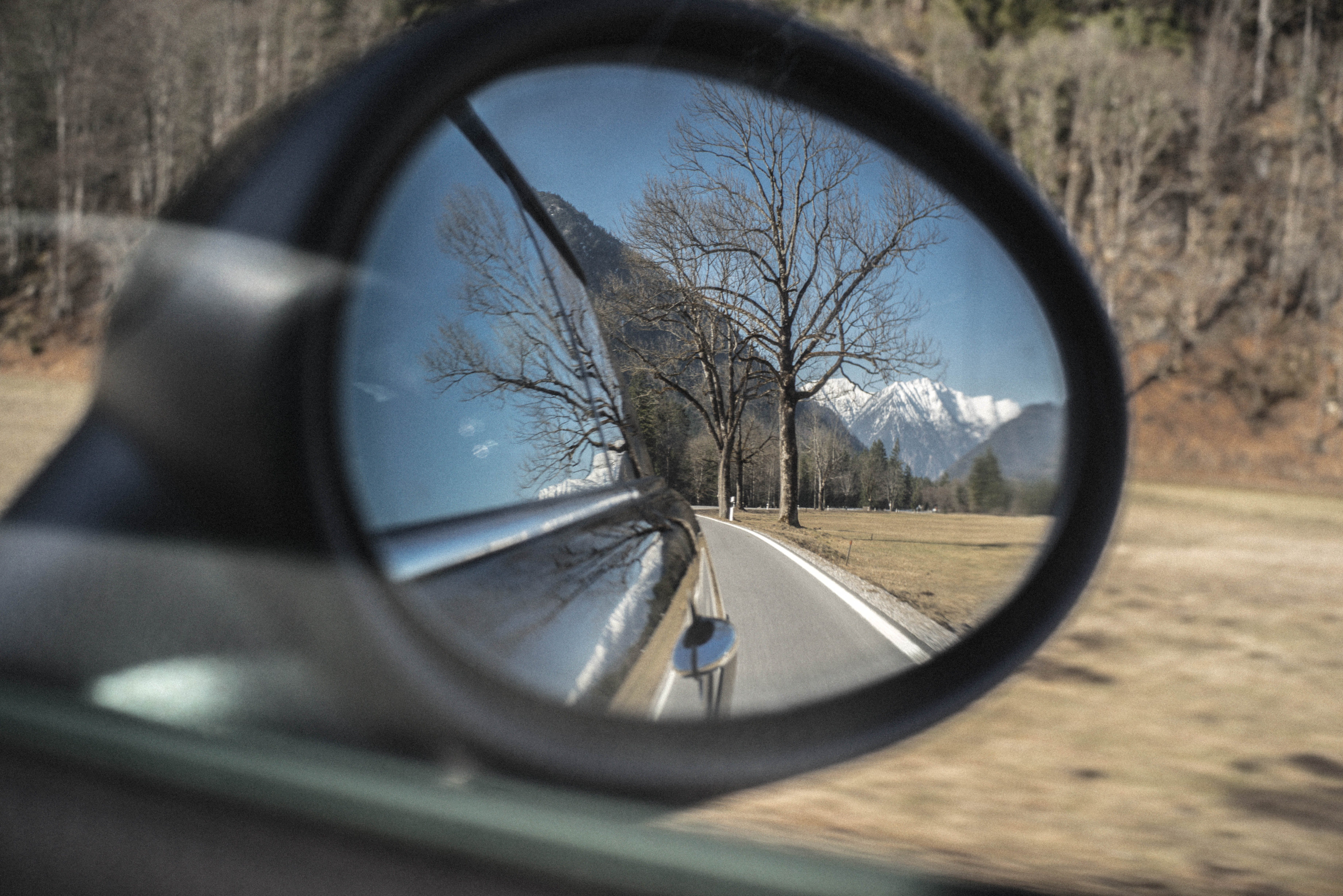 Person Showing Photo of Road on Wing Mirror