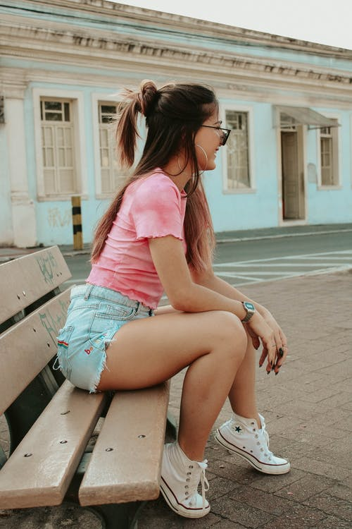 Cheerful young lady resting on bench on street