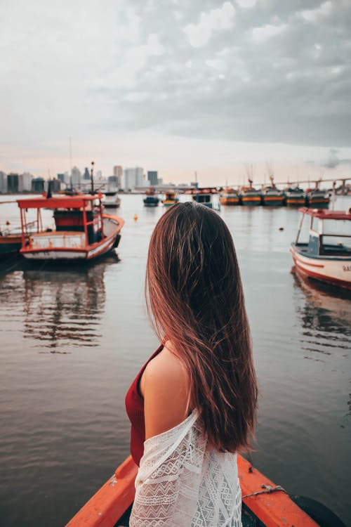 Side view of unrecognizable young female traveler with long hair standing on deck of boat moored in harbor and looking away