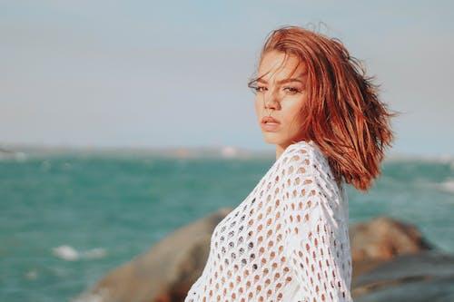 Sensual young woman enjoying summer vacation on seashore on sunny day