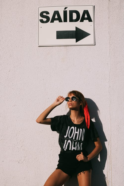 Fashionable young lady leaning on wall and adjusting sunglasses