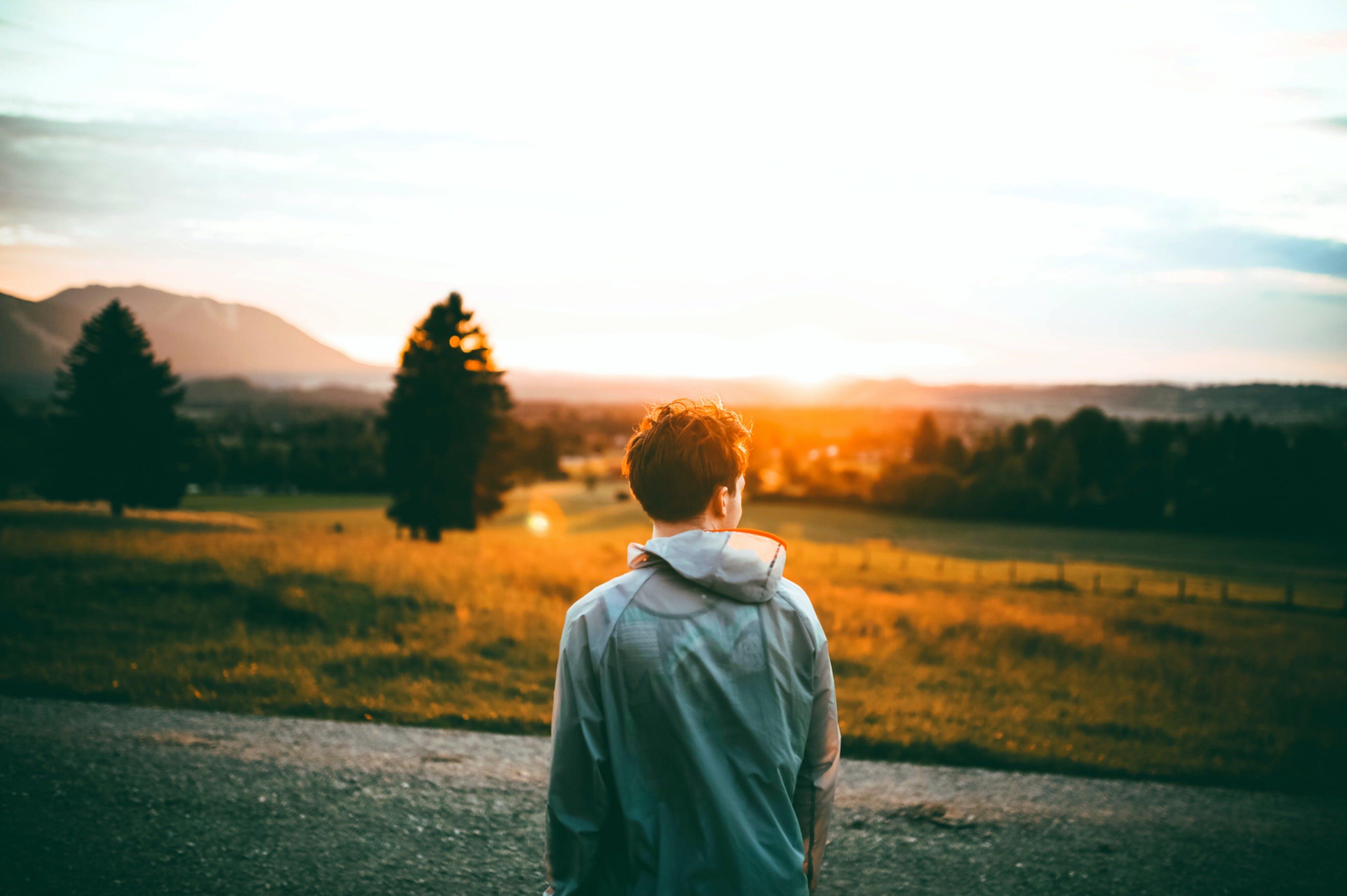 Man Standing Beside Road Facing Sun