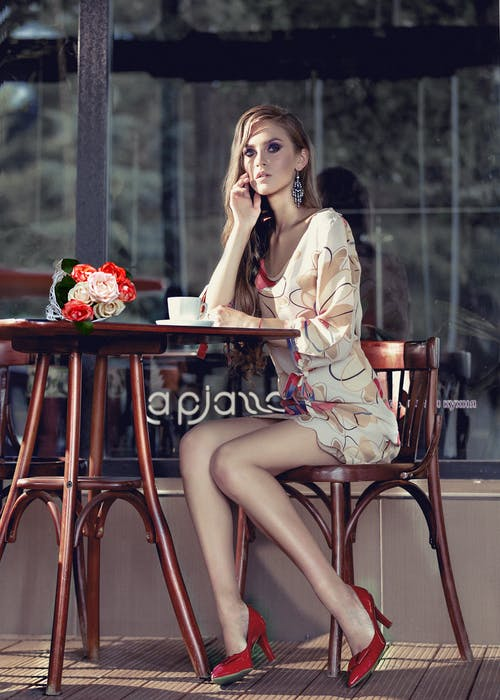 Elegant young woman resting in outdoor cafe during coffee break