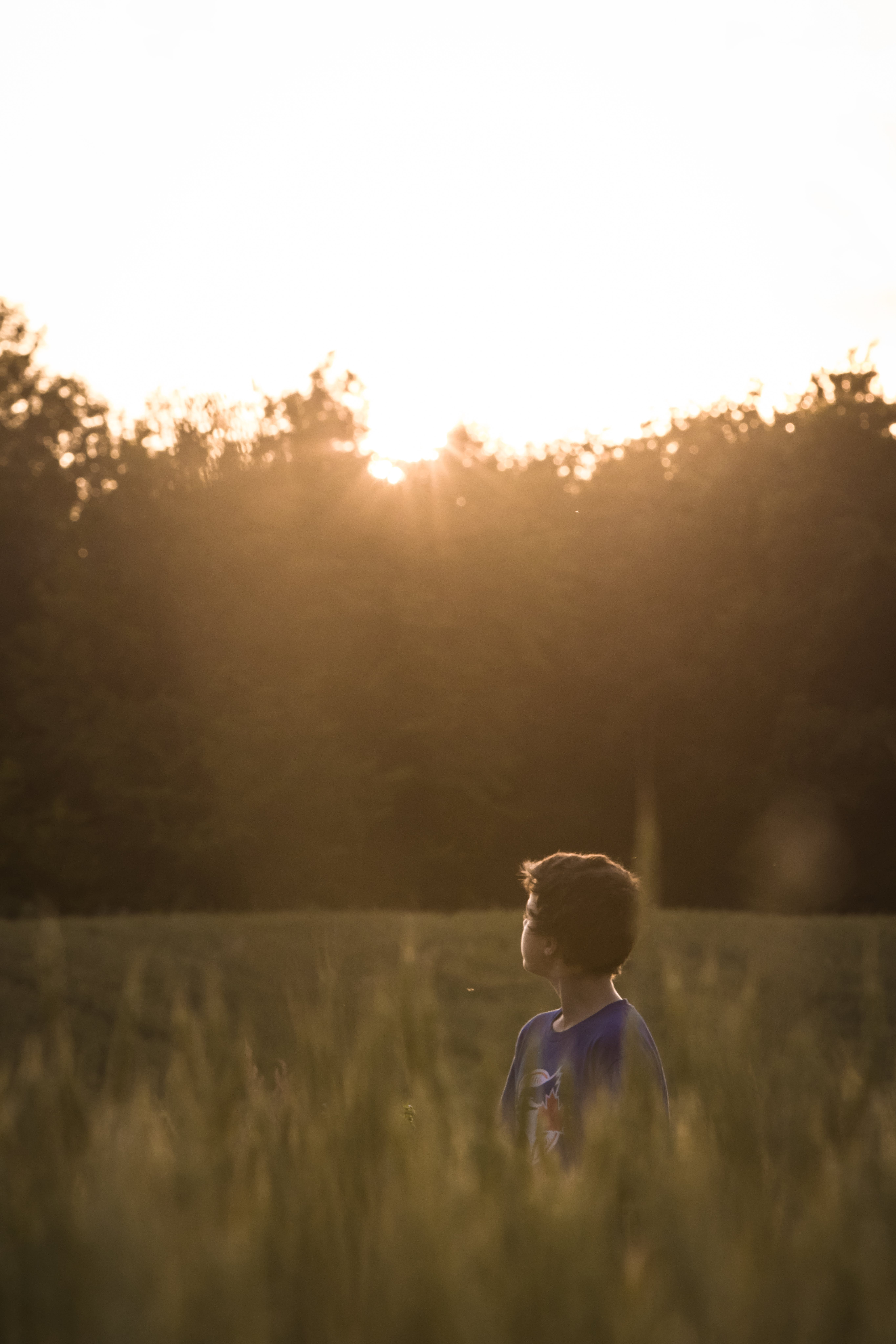 Boy Standing on Grass Field While Looking at the Horizon