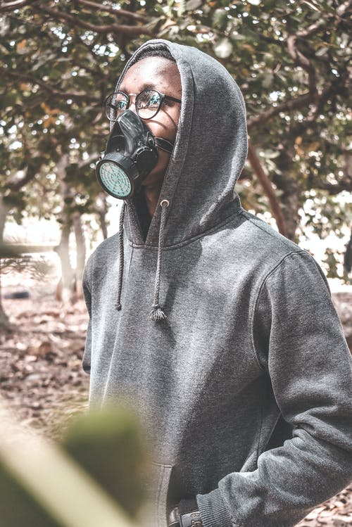 Unrecognizable young black male in casual hoodie and respirator mask standing in park on sunny day and looking up