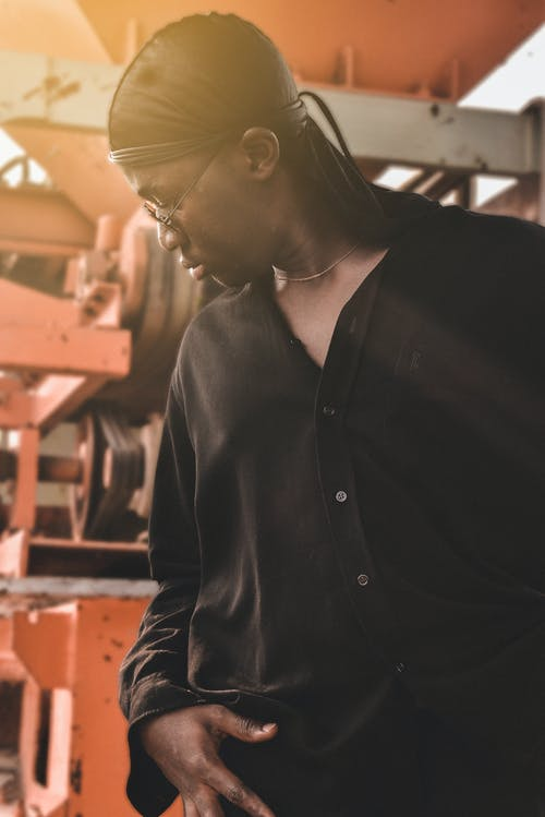 Serious black guy standing near industrial factory