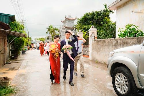 Happy ethnic newlywed couple walking on street during traditional wedding ceremony