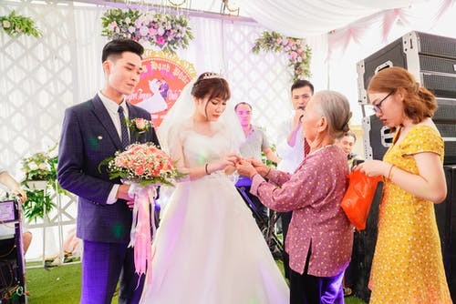 Guests congratulating young ethnic newlyweds during wedding celebration