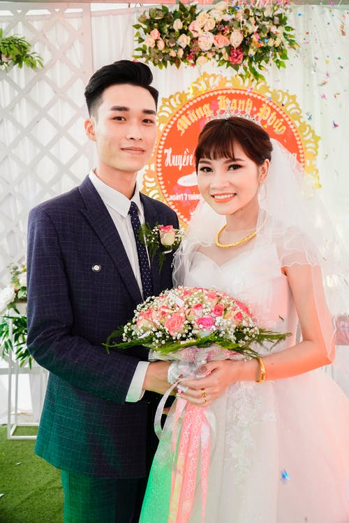 Cheerful ethnic newlyweds standing together during wedding party