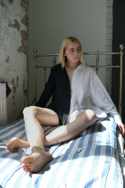 Full length of young barefooted upset female in shirt sitting on bed in shabby room and looking away