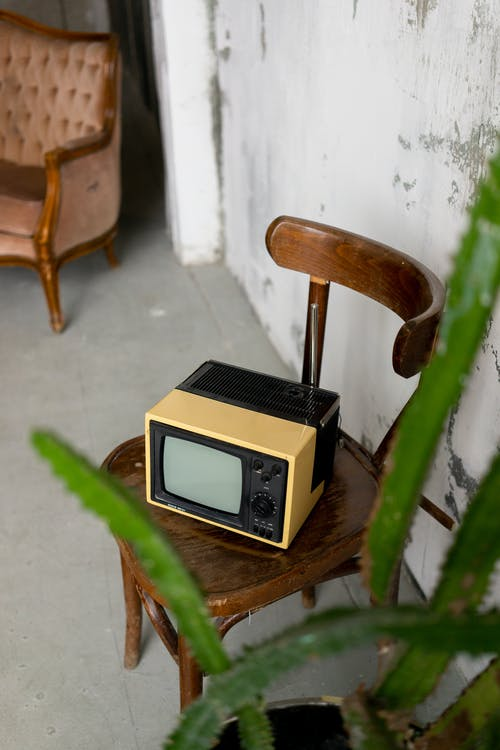 Retro TV placed on chair in room with vintage furniture