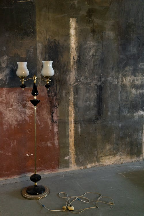 Elegant old fashioned lamp placed on floor in creative studio near shabby uneven wall