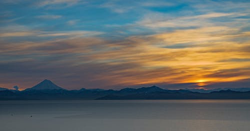 Panorama of multicolored sunset sky glowing above mountains and peaceful sea water at evening