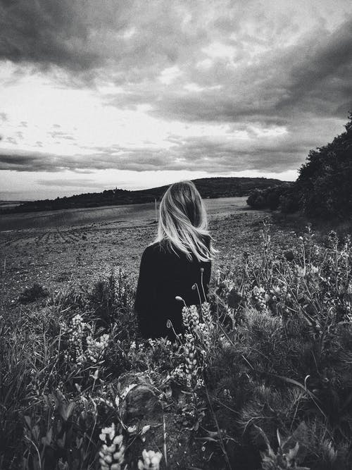 Black and white of blond female standing in tall grass of field under gloomy sky