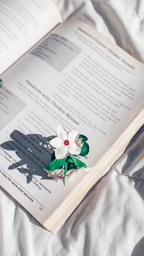 White Paper With Green Flower on White Textile