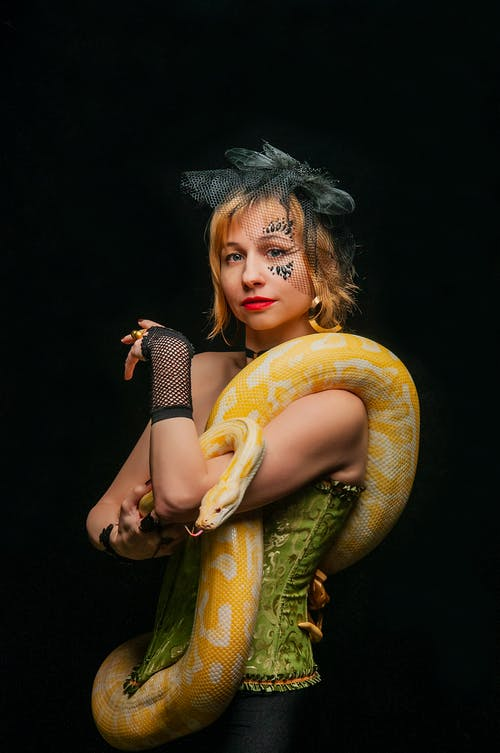 Young female in trendy corset and hat standing with golden python on black background