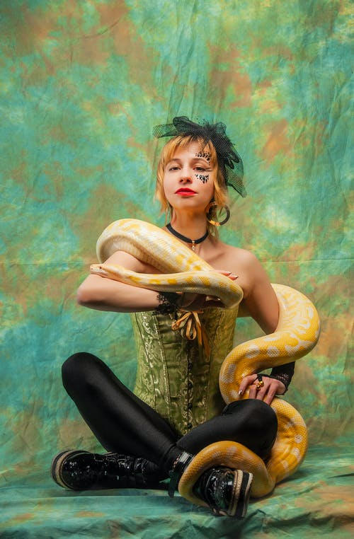 Full length of model in corset and black boots holding yellow python on arms sitting in green studio