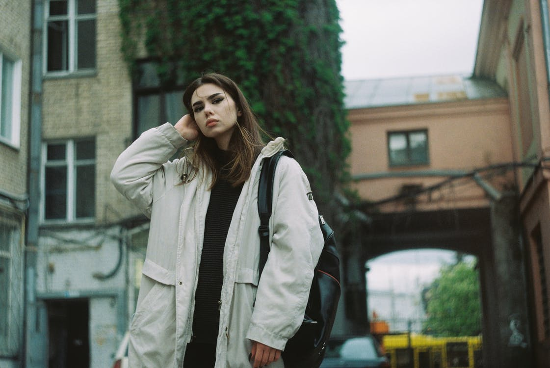 Young woman in stylish outwear standing on street