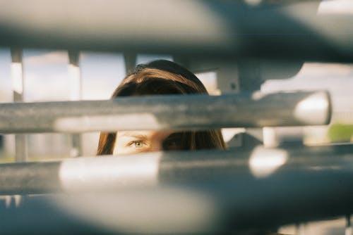 Young woman looking at camera through metal railing