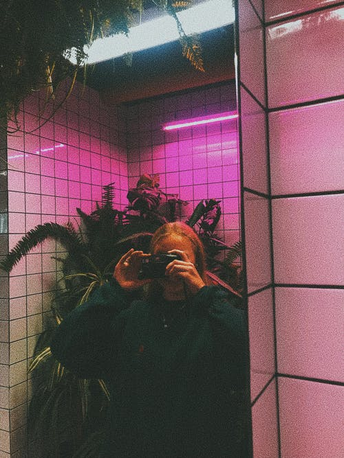 Woman taking photo with camera in mirror