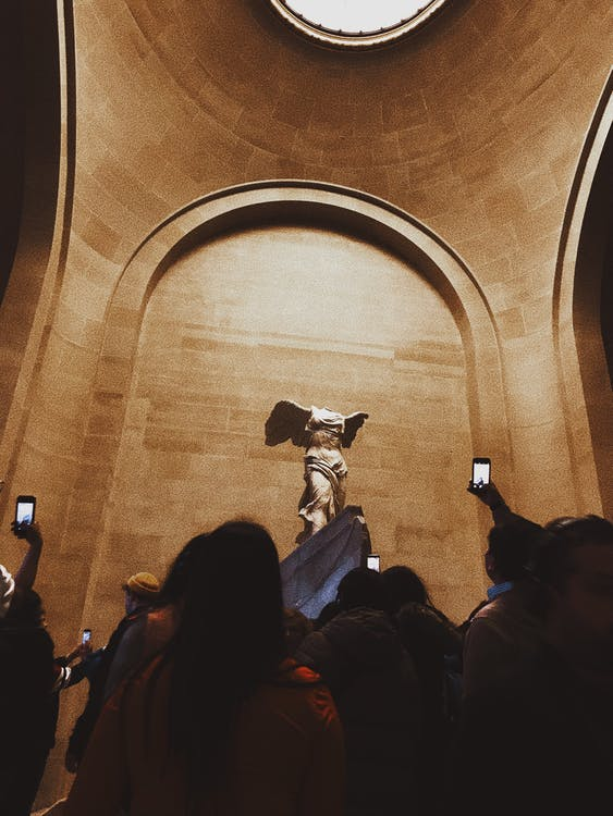 Tourists taking photo of ancient sculpture in museum