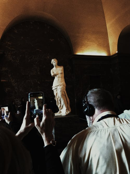 Tourists taking photo of statue in gallery